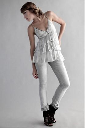 Obcisłe białe spodnie dobrze jest łączyć z luźną górą.